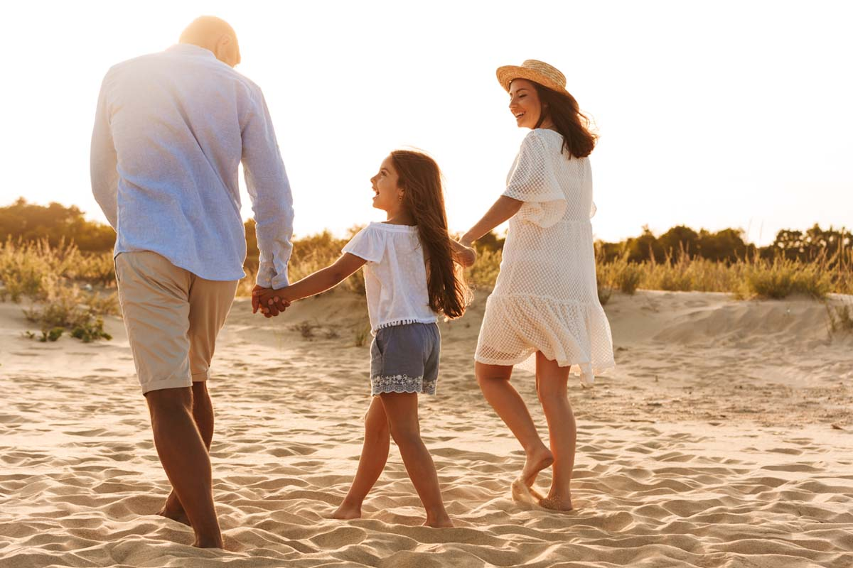 A mom, dad, and little girl holding hands and walking along the sand smiling at each other